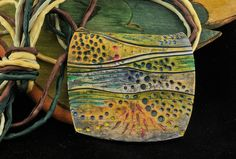 Page McNall/Page's Creations - Starts w/white clay,created lines and patterns. Next, she used black, blue and green PearlEx powders & cured clay. Then used Dockyard wood carving tools to add design and texture. Finally, added Alcohol inks to enhance both colors and harmonize the design. Coupled with hand dyed silk cords.