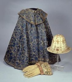 Tudor cloak (c. 1570-90), gloves (1600-30), and hat (1600-10) located in © Museum of London