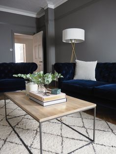 Our living room – adding the final touches with West Elm. Dark grey walls, blue velvet sofa and oak coffee table. Take the tour now.