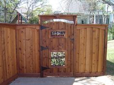 Gorgeous backyard or front yard gate and fence. Love the overhang and Iron accents!