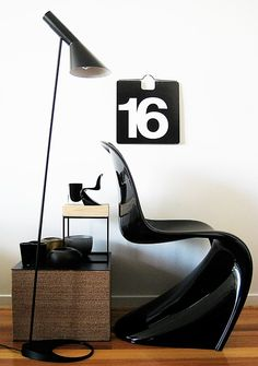 Black things - Here we have the miniature Panton chair with the human-sized version. The AJ Lamp, designed by Arne Jacobsen in 1960. On the cardboard block table are a selection of Dinosaur Designs bowls and an iittala Aalto vase. The wall calendar was designed by Massimo Vignelli.
