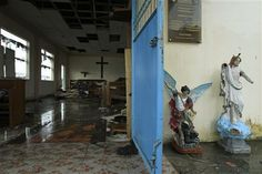 With recovered statues of St. Michael, the Archangel and Jesus Christ at its door, St. Michael The Archangel Chapel has become a makeshift morgue for bodies found in the debris of Typhoon Haiyan in Tacloban, central Philippines, Tuesday, Nov. 12, 2013. There is no functioning morgue here, so people have been collecting the dead and storing them where they can  in this case, St. Michael The Archangel Chapel.  (AP Photo/Wally Santana)