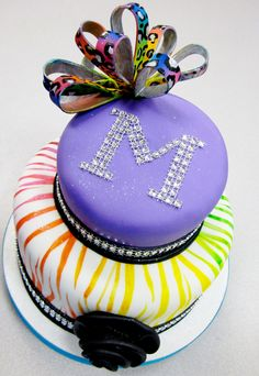 Neon hand painted zebra stripes in a rainbow embellish the bottom tier of this birthday cake. A rhinestone monogram and a cheetah print bow top it off. Cakes By Graham, More Than Just the Icing on the Cake. http://richmondcakes.com/