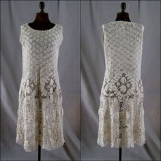 "This charming c.1920 dress is made of handmade Irish crochet lace. It's a sleeveless tunic style flaring out toward the bottom. The crochet starts with a small allover pattern at the top of the dress and gets larger with the added dimension toward the bottom. Tulle inserts circle the dress at about hip height. The scalloped hem is decorated with a delicate ruffle of fine tulle. The color is light ecru. 14"" across shoulders, 34"" bust, 38"" hip, 40"" long from back of neck to hem."