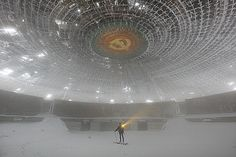 The Buzludzha Monument in Bulgaria. This haunting image shows the abandoned monument filled with snow.
