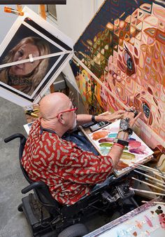 Chuck Close at work painting in his art studio workspace. In 1988, Close was paralyzed following a rare spinal artery collapse; he continues to paint using a brush-holding device strapped to his wrist and forearm.