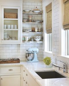 Classic kitchen with white glass-front kitchen cabinets with marble countertops, subway tiles backsplash, stainless steel floating shelves and bamboo roman shades