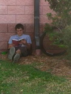 Thomas takes some time out for a reading break on the shady side of the Library.