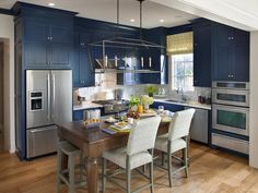 The kitchen and foyer are easily accessible from the great room, creating an open floor plan ideal for entertaining.  Defined by navy hues, a custom-built island and clever storage, the high-tech kitchen offers space for both food prep and casual dining--> http://hg.tv/v8e5