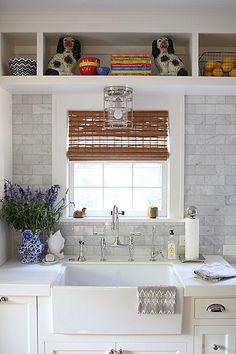 White cabinets, chrome hardware, gray marble backsplash