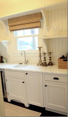 great all white shaker style cabinets with bead board back splash.. lots of open shelving for your collections in the kitchen