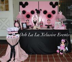Fondo de mesa Minnie decorado con rosetas de papel y como paleta de color rosa y negro.