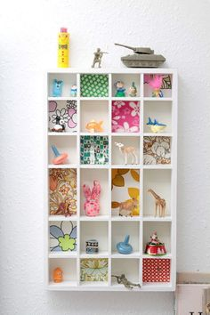 Add squares of scrapbook paper to the inside of cubie storage pieces.  Adorable kids room idea for a pop of fun!