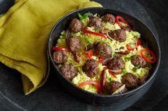 """""""Easy, delicious, and different is how I would describe this casserole. Petite meatballs prepared with ground lamb and seasoned with Moroccan spices are nestled into a baked rice pilaf during the last few minutes of cooking. The rice, scented with saffron, cooks to a rich, golden yellow and is accented with bits of red bell pepper and Medjool dates."""" — Betty Rosbottom, author of Sunday"""