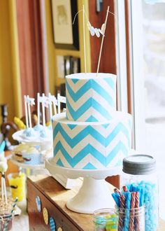 "Chevron Cake! The cake was a 5-inch round atop an 8-inch round dark chocolate cake filled with cookie dough Italian Meringue buttercream and covered in vanilla buttercream, marshmallow fondant and finally chevron ""panels"" made from white and turquoise candy clay."