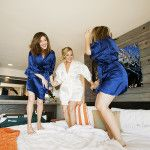 Bride and Bridesmaids jumping on bed.  Amy Clemons Photography
