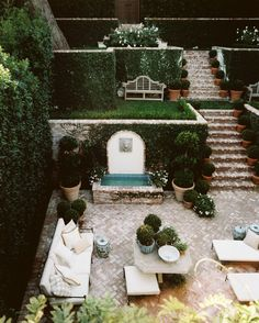 three tiered terraced garden, water feature, group seating, private bench, upper view level, potted clipped topiary, hedge or vine walls