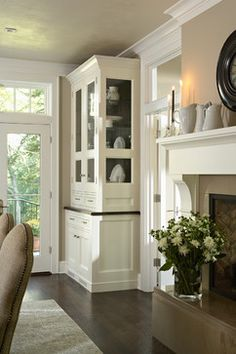 Built-In + White Moulding + Wood Floors + Neutral Paint + Glass Window Above Door to Kitchen