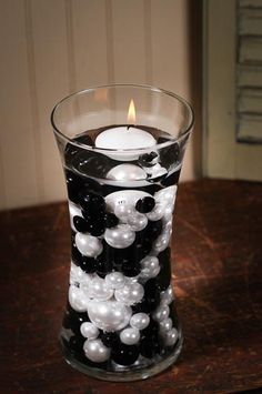 designs by the dollar store...Black and White Faux pearls in the vases with floating candles