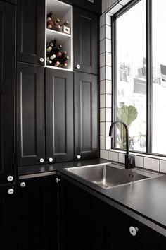 Un mueble de cocina negro y elegante, con un práctico botellero