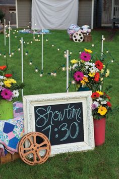 Hang a large drop cloth on the side of the house to serve as a screen, then project the movie onto the cloth. Create a movie marquee by reclaiming a frame and painting a board with chalkboard paint.