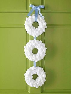 DIY Snowball Wreath — Hot-glue fuzzy white pom-poms over three small foam wreaths, overlapping the pom-poms to fill in any gaps. Cut a length of ribbon and hot-glue the wreaths to the ribbon. Tie extra ribbon into a simple bow and hot-glue it in place at the top. Tip: Look at the wreaths from all angles to make sure you have completely covered the foam bases.