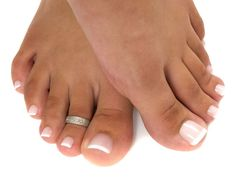 Perfect French pedicure: Isn't it time you treated yourself to a spa visit that leaves you with immaculate toenails? This foot model has perfectly manicured toenails for a very healthy clean look. Her cuticles were professionally removed and beautifully rounded. Her toenails were painted with a soft light pink polish and modestly decorated with thin pretty white tips.