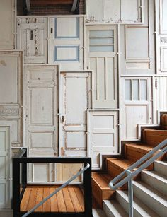 Repurposed wood doors make a cool quirky facade for this stairwell. - There are plenty on doors available at the ReStore for anyone looking to take on a big/unique DIY project like this!