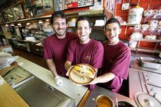 From left, Ali Harb, 34, of Dearborn, Southfield Joe's Coney Island co-owner Ali Bazzi, 24, of Dearborn, and Jaafar Zamat, 21, of Detroit present a Coney Island hot dog at Southfield Joe's Coney Island.