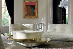 Lenny Kravitz Paris apt living room white glam fur chandelier 1970s brass table Mohammed Ali Warhol