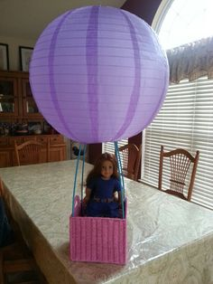 DIY Saige's balloon. A wicker basket, slim PVC poles and a paper lantern. No tutorial, just this photo. I think you could attach the poles to the basket corners with zip-ties.