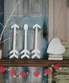 Two DIY projects to decorate a Valentine's mantel: arrows made from paint sticks and a yarn heart!