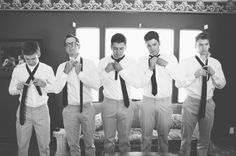 Groomsmen in a line tying their ties.  (Wedding Day Portrait)