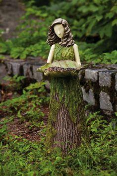 Garden fairy out of tree trunk holding bird feeder