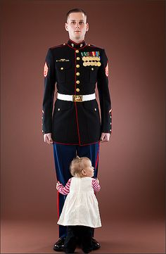 A young Marine just home for the holidays from Afghanistan stands at attention as his one and a half year old daughter hugs her daddy's legs