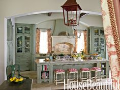 "Turn Your Donald Gardner Home Plan Kitchen into a French-Inspired Green Kitchen    To create beautiful green cabinets for this French-inspired Texas kitchen, designer Michele Allman used an unusual technique. ""We started with Benjamin Moore's November Rain and then added layer upon layer of pigment and glaze to build up this crusty finish"""