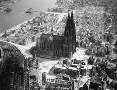 The Cologne cathedral stands tall amidst the ruins of the city after Allied bombings, 1944.