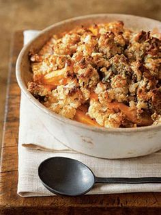 Pumpkin and cauliflower casserole topped with a mix of roasted pumpkin seeds, bread crumbs, herbs, and goat cheese.