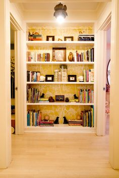 wallpaper shelves, shelving at end of hall, awesome bookcase, decorating book shelves, end of hallway decor