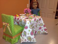 "DIY 18"" Doll Furniture: Table is wood stool from craft store. Chairs are make from 1""x6"" board. Cut 4 5"" pieces for seat, 1 10"" for back. Stack seat pieces to make solid block. Glue/nail together. Put fiberfill on top for cushion and cover with fabric using heavy duty stapler. Same for back. Glue/nail back to seat. Add skirt, bow, and glue felt to bottom to cover staples. Plates are plastic sushi dishes, food is erasers, napkin rings are beads strung on heavy thread."