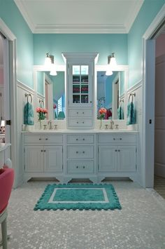 Turquoise and white and bright lighted bathroom with double sinks, mirrors, and plenty of storage