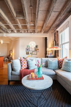 An eclectic mix of exposed beams, a gray chevron rug, sofa and round coffee table