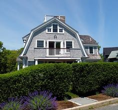 """This is a traditional Dutch colonial with widow's walk. This American style originated in homes built by German, or """"Deutsch"""" settlers in Pennsylvania as early as the 1600s. A hallmark of the style is a broad gambrelroof with flaring eaves that extend over the porches, creating a barn-like effect."""