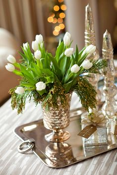 A silver tea tray holds a bouquet of fresh tulips