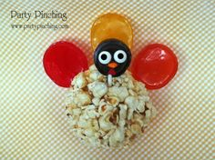 Turkey Popcorn Ball ~ Super sweet popcorn treat!  This little turkey is made from a popcorn ball and lollipops!  The head is a Tootsie pop with candy eyes and sprinkles for the rest of the face. Great for the kids table as a placecard too!