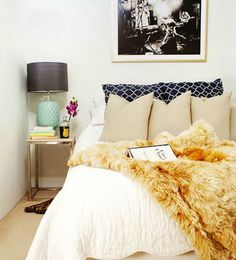 I love the pale blue lamp with the dark shade, flowers, and the touch of gold via the plush throw. Graphic + feminine loveliness.