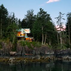 Gambier Island House by OMB cantilevers over a rocky cliff face.