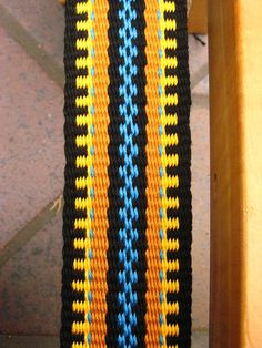 """Usually, I do not put patterns on paper before I set up my loom. I warp and design as I go. The golden sunshine and bright blue skies of the day were reflected in the colors of this guitar strap. I wove it while enjoying myself immensely at the Redwood Mountain Faire in Felton, CA, June of 2014. I called it """"Vibe of the Day"""".  ~Annie MacHale"""