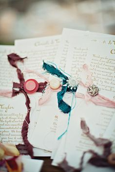 Vintage letter-pressed ceremony programs tied with torn pieces of silk | photo by Jillian Mitchell