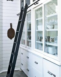 This pantry takes advantage of 12-foot ceilings with three kinds of storage: drawers, shelves with sliding glass fronts and upper cabinets with custom steel-cut panels that are similar to those on the house's stair railings. A custom 9-foot ladder from putnamrollingladder.com rolls across on a steel rod. | Photo: Jean Allsopp